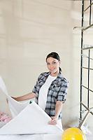 Portrait of mid adult architect holding blueprints at construction site