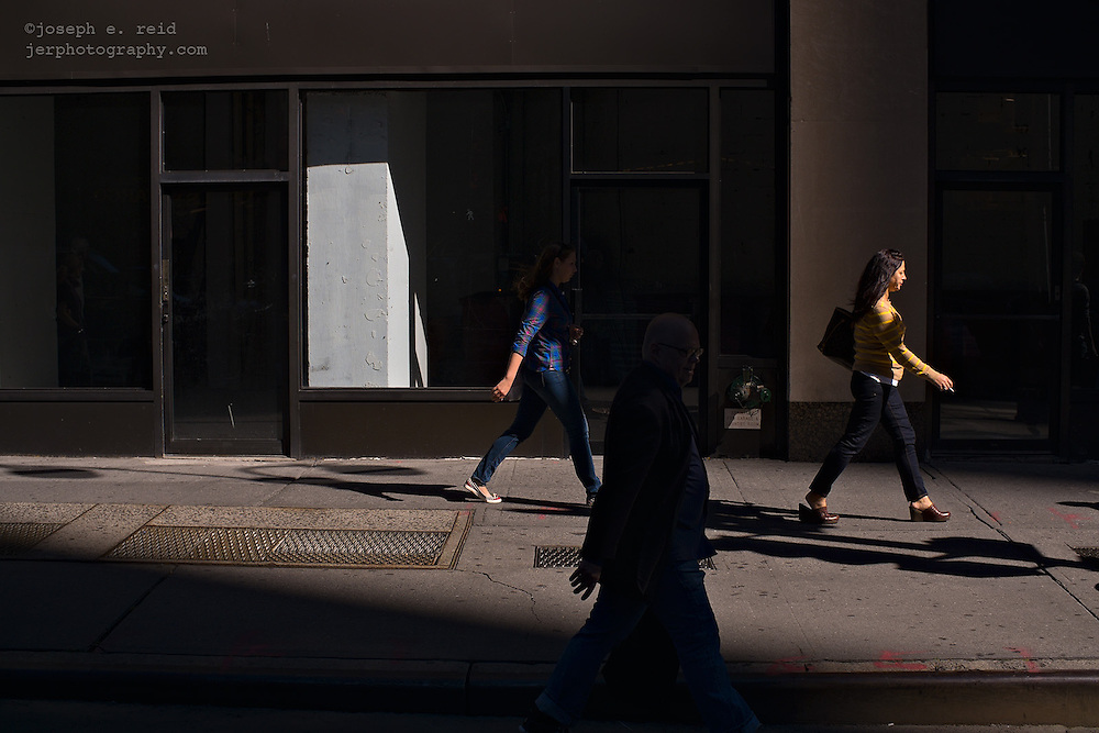 People passing empty storefront