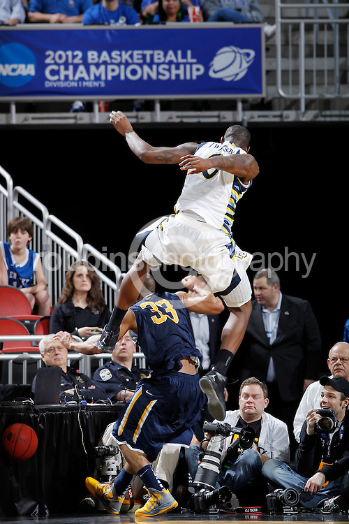 Jamil Wilson #0 of the Marquette Golden Eagles tries to avoid photographers and the press table as he jumps over Jewuan Long #33 of the Murray State Racers during the third round of the NCAA men's basketball championship on March 17, 2012 at KFC Yum! Center in Louisville, Kentucky. Marquette advanced with a 62-53 win. (Photo by Joe Robbins)