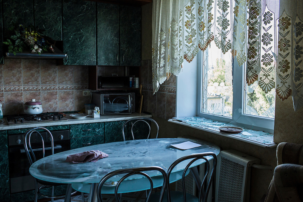 A kitchen window is broken after the apartment building was hit by a suspected grad rocket strike on Tuesday, July 29, 2014 in Donetsk, Ukraine.