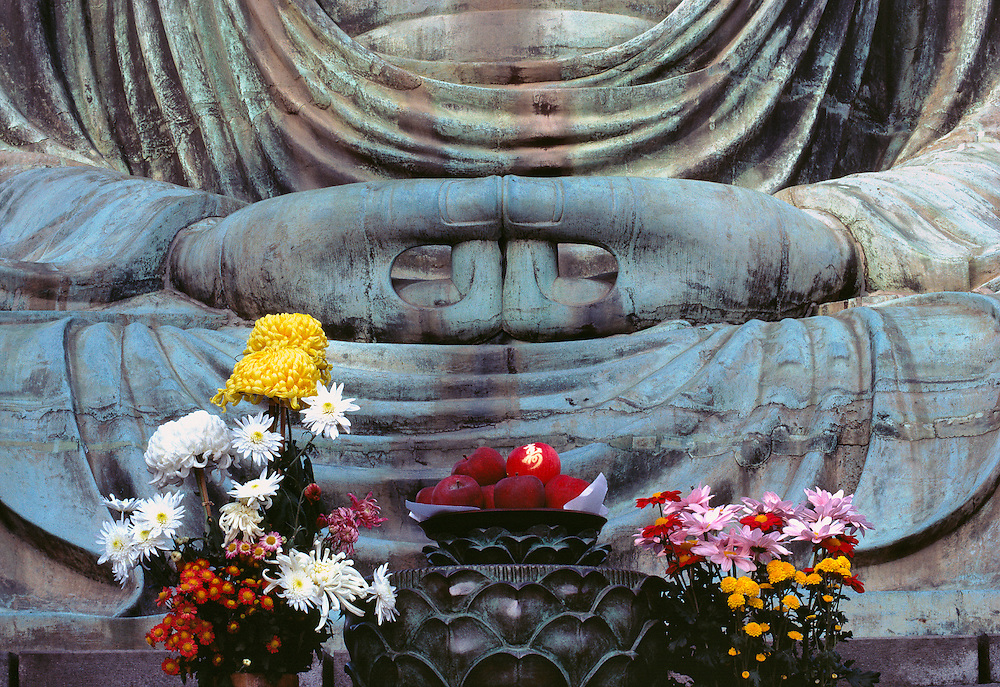 Fruit and floral offerings are placed at the base of the Great Buddha at Kamakura, Japan.