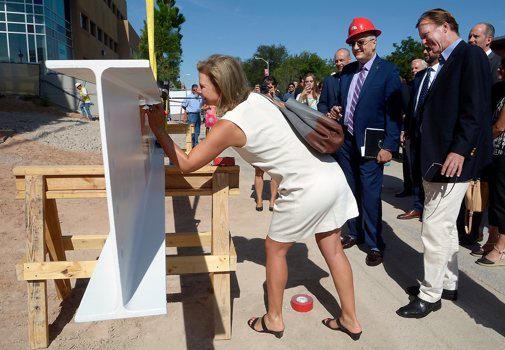gbs072617c/BUSINESS -- Alumni donor Sonnet McKinnon signs the final beam of the UNM Anderson School of Management's new building, left, as Chaouki T. Abdallah, acting president of The University of New Mexico, center, and her husband Ian McKinnon, right, wait to sign during the topping off ceremony on Wednesday, July 26, 2017. (Greg Sorber/Albuquerque Journal)