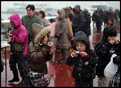 Children eat Oysters in the snow at the Matsushima Oyster festival which was hit by the tsunami in March 2011. Japan is experiencing some of the Heavest snow falls for years on the first day of Spring, Saturday February 4, 2012. Photo By Andrew Parsons/ i-Image..