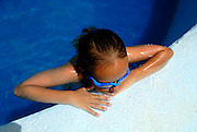 Australian tourist child (9 years old) resting on side of swimming pool. Sanur, Bali, Indonesia.
