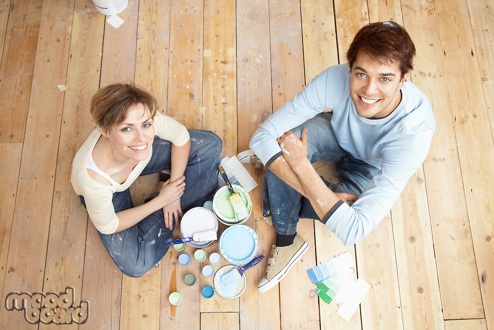 Couple sitting on floorboards amongst paint pots view from above