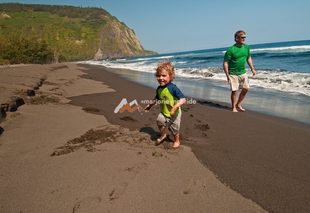 Father and son playing on a black sand beach in Waipi'o Valley, North Shore, the Big Island, Hawaii.