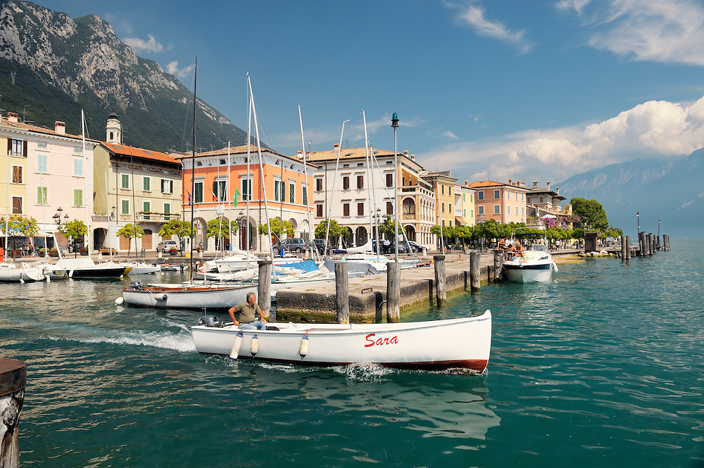 The holiday resort town of Gargnano on Lake Garda, Lombardy, Italy. Boat leaving the harbour. Lago di Garda.