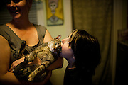 Barbara Dolan holds the family cat, Francey Pants, while her 10-year-old son Drew Neiburger attempts to get as much of the cat's head into his mouth Saturday Jun. 29, 2013, in Oak Park, Ill. Rob Hart/RobHartPhoto.com