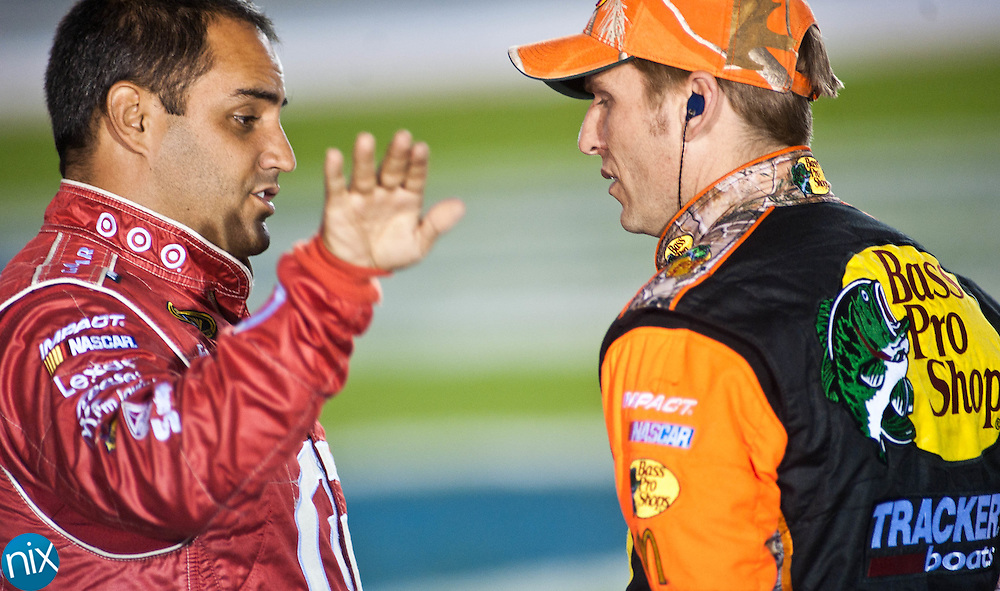 Juan Pablo Montoya talks with Jamie McMurray prior to qualifying for the Bank of America 500 during  Bojangles Pole Night at Charlotte Motor Speedway Thursday night. (Photo by James Nix)