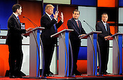 Republican U.S. presidential candidate Donald Trump shows off the size of his hands as rivals Marco Rubio (L), Ted Cruz (2nd R) and John Kasich (R) look on at the start of the U.S. Republican presidential candidates debate in Detroit, Michigan, U.S., March 3, 2016.   REUTERS/Jim Young