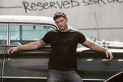 very good looking muscular auto mechanic with grease and dirt on his face leaning against a vintage car