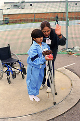 Coach and young girl with disability from India taking part in Mini games sports event held at Stoke Mandeville Stadium,