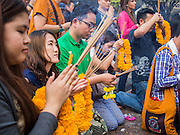 31 DECEMBER 2013 - BANGKOK, THAILAND:    Women pray on New Year's Eve at Erawan Shrine in Bangkok. Hundreds of thousands of people pack into the Ratchaprasong Intersection in Bangkok for the city's annual New Year's Eve countdown. Many Thais go the Erawan Shrine and Wat Pathum Wanaram near the intersection to pray and make merit.  PHOTO BY JACK KURTZ