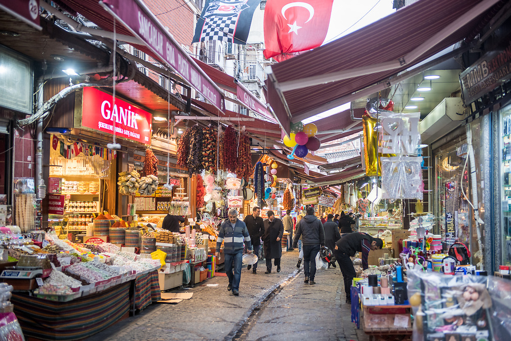 Awnings provide cover for shoppers as they walk along pathway lined with stores and stalls selling goods in outdoor market, Istanbul, Turkey