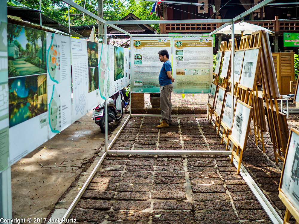 20 MAY 2017 - BANGKOK, THAILAND: A Thai man looks at an exhibit about the historic roots of Pom Mahakan in a community square in Pom Mahakan. The final evictions of the remaining families in Pom Mahakan, a slum community in a 19th century fort in Bangkok, have started. City officials are moving the residents out of the fort. NGOs and historic preservation organizations protested the city's action but city officials did not relent and started evicting the remaining families in early March.        PHOTO BY JACK KURTZ