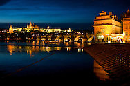 Flood lights illuminate the buildings along the Vlatva River as night descends over Prague.