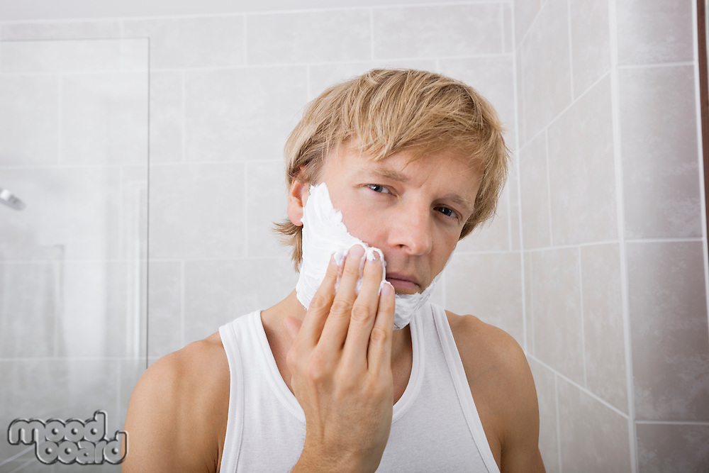 Portrait of mid-adult man applying shaving cream in bathroom