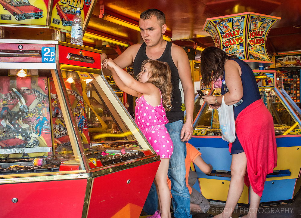 """A young girl pushes another """"ten pee"""" into a game. Arcade games are a classic and all-times favourite at fun fairs."""