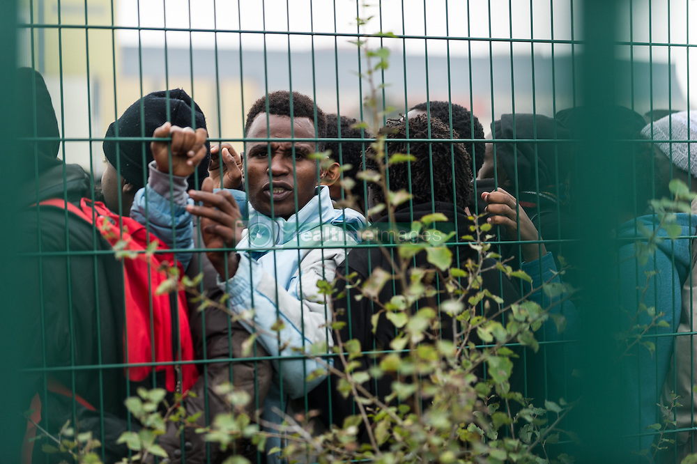 October 24, 2016 - Calais, France - Migrants stand in a line to register themselves in near the Calais Jungle, on October 24, 2016. After registration, the migrants are distributed on buses. The refugee camp on the coast to the English Channel is to be cleared today. The approximately 8,000 refugees are distributed after the registration by busses to various reception centers in France, on October 24, 2016. (Credit Image: © Markus Heine/NurPhoto via ZUMA Press)