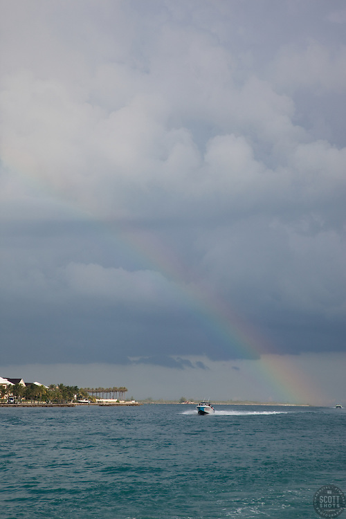 A boat in the Bahamas under a rainbow.