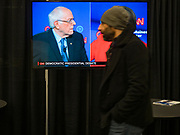 14 JANUARY 2020 - DES MOINES, IOWA: A man walks past the debate being shown on a flat screen TV in the media work room at the CNN Democratic Presidential Debate on the campus of Drake University in Des Moines. This is the last debate before the Iowa Caucuses on Feb. 3.    PHOTO BY JACK KURTZ