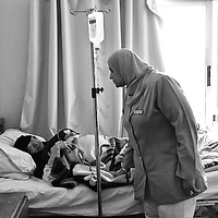 Egypt / Syrian refugees / Syrian refugee Samia Gasen, 70-years-old, lays in a hospital bed as nurse Waafa Mohamed Abd Al Samaea comforts her at the Mahmoud Charity Hospital in Cairo, Egypt, Tuesday, May 28, 2013. Samia who has a tumor in her uterus arrived in Cairo almost 2 months. Samia's home in Damascus was destroyed 10 months ago and her nephew was killed in January when his house was destroyed.   / UNHCR / Shawn Baldwin / May 2013