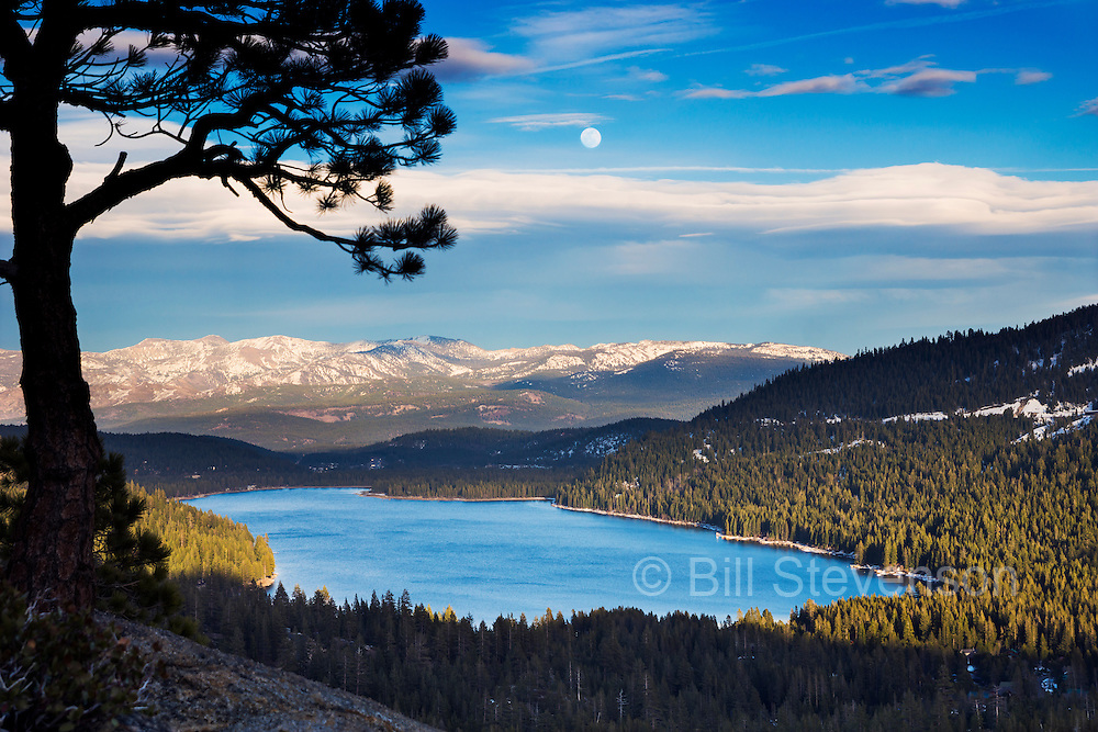 A photo of the full moon rising over Donner Lake near Truckee, CA. The moon is rising above lenticular clouds and the Carson Range of the Sierras.