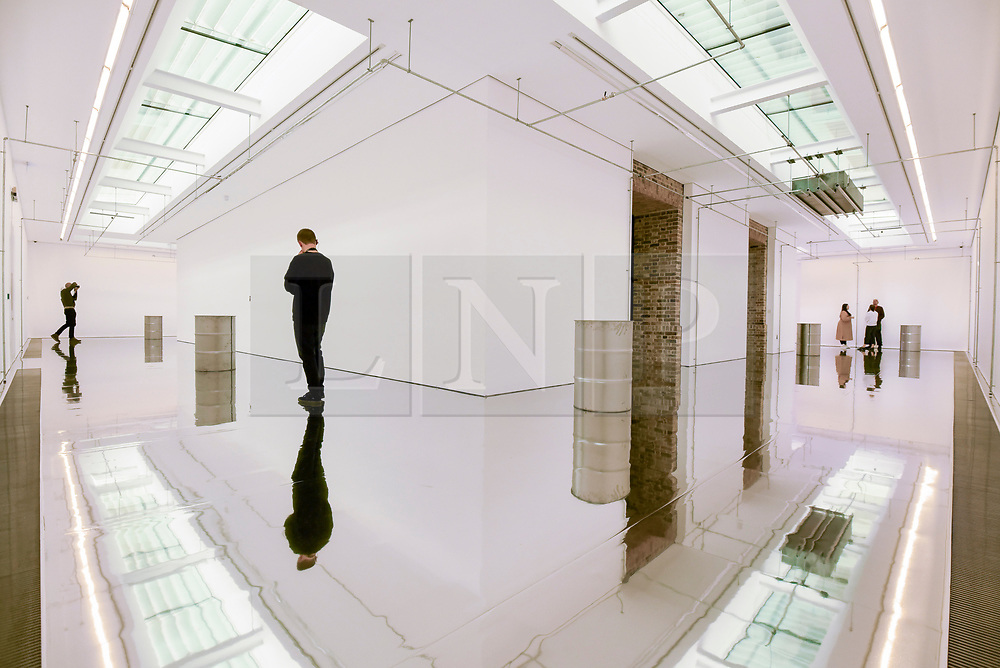 """© Licensed to London News Pictures. 07/11/2019. LONDON, UK.  General view of gallery space at the preview of """"On Venus"""" by Patrick Staff, a site-specific exhibition commissioned by the Serpentine Sackler Gallery.  Altered lighting and reflective flooring combined with natural and synthetic liquids leaking from ceiling piping into steel barrels forms the major installation.   The exhibition, which also includes etchings and video work, runs 8 November to 9 February 2020.  Photo credit: Stephen Chung/LNP"""