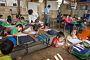 "25 FEBRUARY 2008 -- MAE SOT, TAK, THAILAND: The children of Burmese migrants take classes at the Blue Sky School near the garbage dump in Mae Sot, Thailand. The students at the school are all the children of Burmese migrants who work in the garbage dump, sorting and selling what they find amid the trash. There are millions of Burmese migrant workers and refugees living in Thailand. Many live in refugee camps along the Thai-Burma (Myanmar) border, but most live in Thailand as illegal immigrants. They don't have papers and can not live, work or travel in Thailand but they do so ""under the radar"" by either avoiding Thai officials or paying bribes to stay in the country. Most have fled political persecution in Burma but many are simply in search of a better life and greater economic opportunity.  Photo by Jack Kurtz/ZUMA Press"