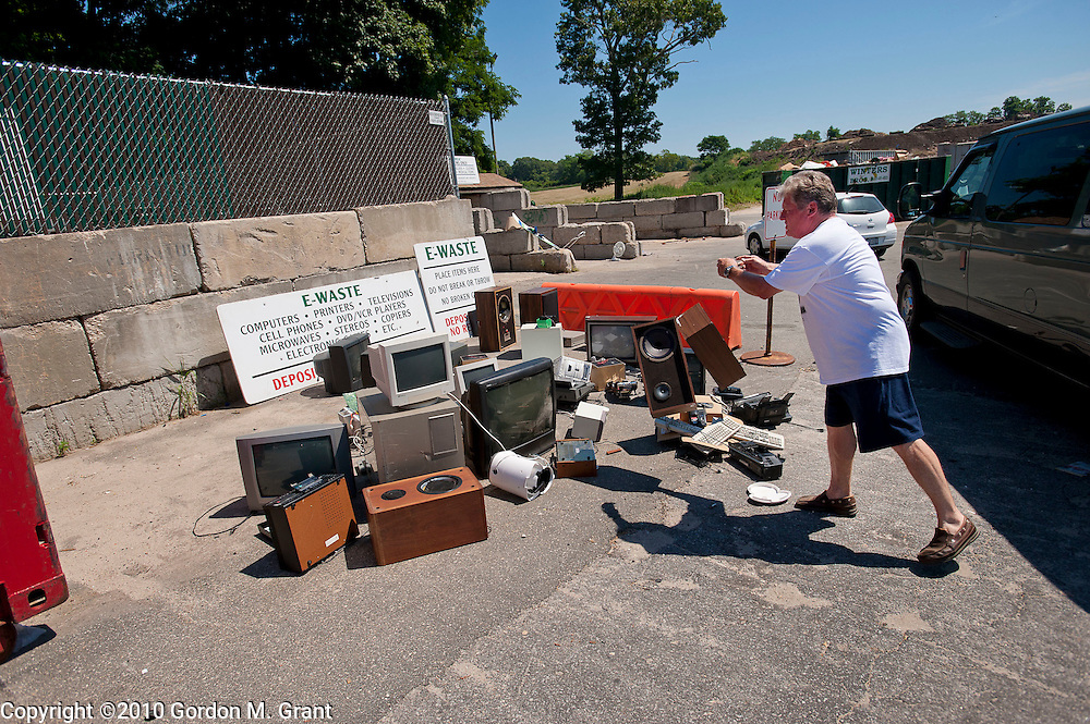 Shelter Island, NY - 7/5/10 - Bob Gates of Shelter Island puts items in the E-Waste area of the Shelter Island Town Recycling Center on Shelter Island, NY, July 5, 2010. CREDIT: Gordon M. Grant for The Wall Street Journal.