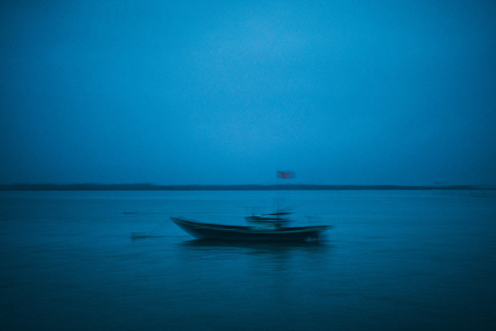 A blurry image of a small fishing boat on the water at the break of dawn in Hoi An, Vietnam.