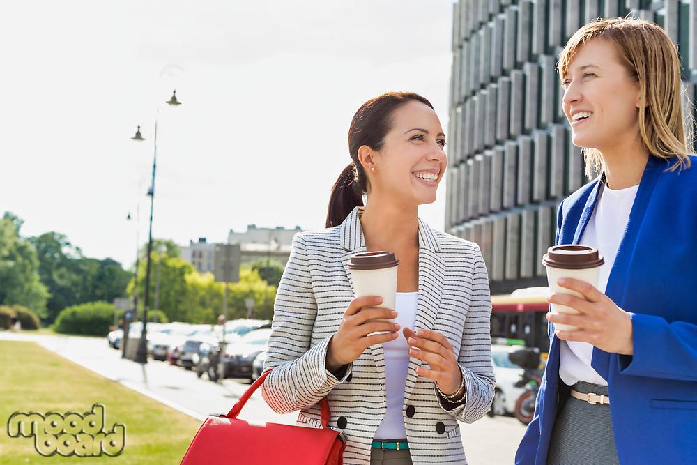 Businesswomen walking while talking outside office building