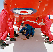 Officer pilots of the elite 'Red Arrows', Britain's prestigious Royal Air Force aerobatic team, lean aginst a wing of their Hawk jet in a pre-flight briefing while a member of their ground crew positions some wheel chocks. The highly-skilled engineer is known as a 'Blue' but the 'Reds' discuss  flight plans. Eleven trades skills are imported from some sixty that the RAF employs and teaches. It is mid-day and only their flying boots and red legs are seen with the RAF roundel emblem is on the underside of the wing. The better-educated officers in the armed forces enjoy a more privileged lifestyle than their support staff. In the aerobatic squadron, the Blues outnumber the pilots 8:1. Without them, the Red Arrows couldn't fly. SOme of the team's Hawks are 25 years old and their air frames require constant attention, with increasingly frequent major overhauls due.