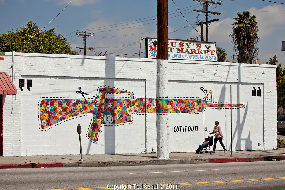 Street art in Los Angeles..L.A. has become the new ground zero for avant-guard and cutting edge street and graffiti. Artist from around the world now come to L.A. to post their work..A flower gun street art piece by Cyrcle on Santa Monica Blvd.