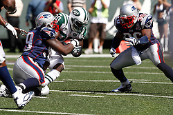 Sept 20, 2009; East Rutherford, NJ, USA;  New York Jets running back Thomas Jones (20) is tackled after a run during the first half of their game against the New England Patriots at Giants Stadium.