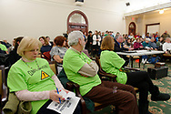 Mineola, New York, USA. 15th Feb, 2019. Activists wearing neon green Climate Emergency ! shirts sit in front row of audience during NYS Senate Public Hearing on Climate, Community & Protection Act, Bill S7253, sponsored by Sen. Kaminsky, Chair of Senate Standing Committee on Environmental Conservation. This 3rd public hearing on bill to fight climate change was on Long Island.