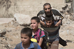 &copy; Licensed to London News Pictures. 15/06/2017. Mosul, Iraq. A Mosul resident carries a disabled relative across open ground, under constant threat of being shot by ISIS snipers, as they escape Islamic State territory to reach Iraqi Army positions.<br /> <br /> Despite heavy fighting between the Islamic State and Iraqi Security Forces many civilians have started to leave ISIS territory in West Mosul. Mosul residents, many of whom have been in hiding in their homes since the start of the West Mosul Offensive, often have to run through ISIS sniper and machine gun fire to reach the safety of Iraqi Security Forces positions. Photo credit: Matt Cetti-Roberts/LNP