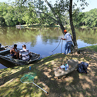 Brian Sandeford, from left, Shane Morris and Justin Rakestraw get ready to leave the shore and continue removing dead fish from a small lake on Strain Street in Tupelo on Tuesday.