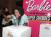 "Adrienne Moore, of Orange is the New Black, admires the Ava DuVernay one-of-a-kind Barbie at the Variety Power of Women event, Friday, April 24, 2015, in New York, where Ava was honored as a Barbie ""Shero.""  Ava DuVernay, along with Emmy Rossum, Eva Chen, Kristin Chenoweth, Sydney ""Mayhem"" Keiser, and Trisha Yearwood, are the first ever Barbie Sheroes, which celebrates women who are inspiring girls.  (Photo by Diane Bondareff/Invision for Barbie/AP Images)"