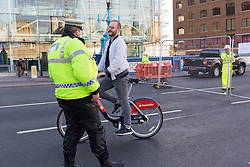 © Licensed to London News Pictures. 01/10/2016. LONDON, UK.  A Police officer speaks to a cyclist who has been cycling on the pavement on Tower Bridge. Tower Bridge closes to traffic today for three months for major renovations and repair. Pedestrians are still able to walk across the bridge. Photo credit: Vickie Flores/LNP