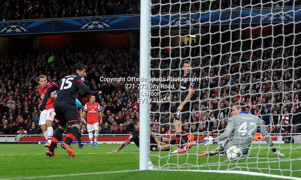 03/10/2012 - UEFA Champions League Football - Group Stage - 2012-2013 - Arsenal v Olympiacos - Lukas Podolski (L) watches on as he scores Arsenal's second goal. - Photo: Charlie Crowhurst / Offside.
