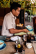 Cambodian butler serving lunch