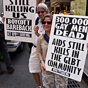 During the Gay Pride Parade ACTUP demonstrator holds sign AIDS meds alone won't stop the epidemic Condoms Save Lives! AIDS is Still killing Us! Boycott Barebacks. Bareback Bottsoms 400% More Likely to Get HIV!