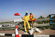Foreign guest worker directing traffic at a construction site in Dubai, United Arab Emirates.
