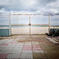 """L'ingresso principale dall'interno dell'ex centro di permanenza temporanea """"Casa Regina Pacis"""" a San foca (LE) ormai in disuso. 21/02/2010 (PH Gabriele Spedicato)..I Centri di permanenza temporanea (CPT), ora denominati Centri di identificazione ed espulsione (CIE), sono strutture istituite in ottemperanza a quanto disposto all'articolo 12 della legge Turco-Napolitano (L. 40/1998) per ospitare gli stranieri """"sottoposti a provvedimenti di espulsione e o di respingimento con accompagnamento coattivo alla frontiera"""" nel caso in cui il provvedimento non sia immediatamenti eseguibile."""