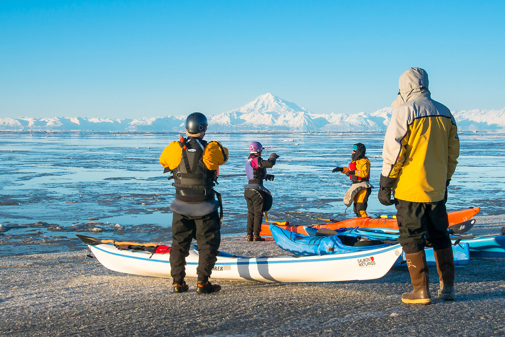 Kayakers prepare to paddle among the ice flows of Cook Inlet with Mt. Redoubt in the background. M.R.