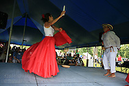 Carmen Dence performs a traditional slow Colombian cumbia dance with candles and a male partner at the Festival of Nations celebration in Tower Grove Park; St. Louis, Missouri.