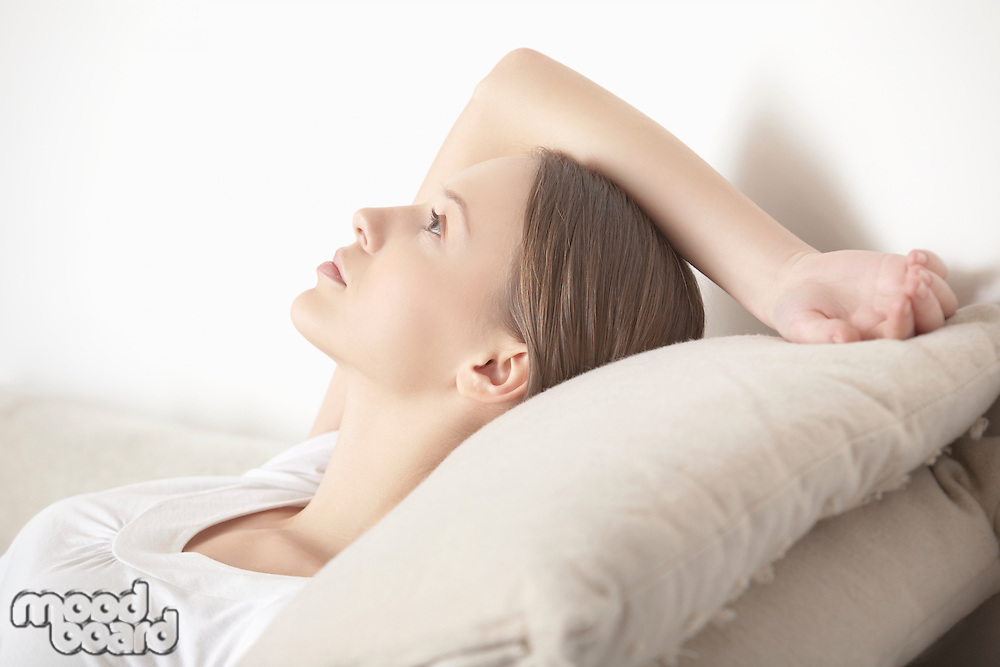 Young woman lies relaxing with hand behind head