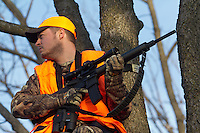 DEER HUNTER WEARING BLAZE ORANGE USING A BLACK RIFLE FROM A LADDER STAND