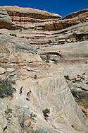 boy, mom and sister hiking down sleep slope in natural bridges monument in Utah